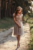 Ung kvinna i krans som barfota går i skog Arkivfoto