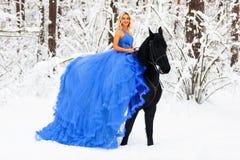 Ung kvinna i lång klänning som rider en häst i vinter arkivfoto