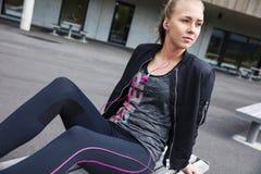 Ung kvinna i lyssnande musik för sportdräkt på bänk royaltyfri fotografi