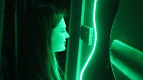 Ung kvinna i mörkret som ser in i spegeln med neonlampor Klubba den ungdomliga härliga flickan för modegåta som ler leende stock video