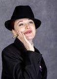 Ung kvinna i manlig stil med den mini- cigarren på grå bakgrund, flicka i dräkt och band för man` s, den vita skjortan och hatten royaltyfria foton