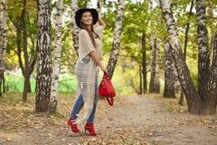 Ung kvinna i modejeans och röd påse som går i höst Fotografering för Bildbyråer