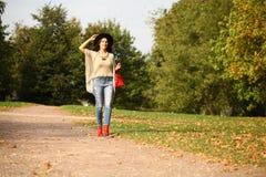 Ung kvinna i modejeans och röd påse som går i höst Arkivfoton