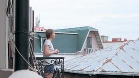 Ung kvinna i morgonen och att dricka te eller kaffe på en balkong arkivfilmer