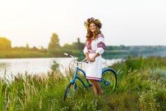 Ung kvinna i nationell ukrainsk folkdräkt med cykeln Fotografering för Bildbyråer