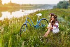 Ung kvinna i nationell ukrainsk folkdräkt med cykeln Royaltyfria Bilder