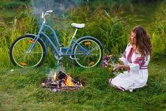 Ung kvinna i nationell ukrainsk folkdräkt med cykeln Arkivfoton