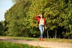 Ung kvinna i omslag och jeans för mode som rött går i autu arkivbilder