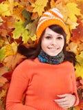 Ung kvinna i orange sidor för höst. Arkivbild