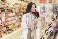 Ung kvinna i parfymeriaffär Arkivbild