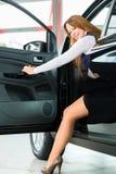 Ung kvinna i plats av automatiskn i bilåterförsäljare Arkivfoto