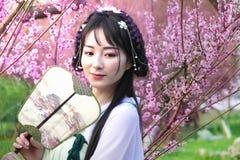 Ung kvinna i plommonträdgården royaltyfri foto