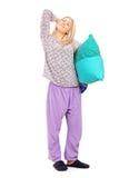 Ung kvinna i pyjamas som rymmer en kudde och sträcker sig Arkivfoton