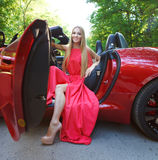 Ung kvinna i röd klänning som placerar i en sportbil royaltyfria foton