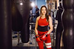Ung kvinna i röd sportkläder och boxninghandskar, drev med ett boxas päron i en mörk idrottshall arkivbild