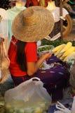 Ung kvinna i röda säljande grönsaker Arkivbilder
