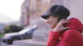Ung kvinna i rött omslag och gråa locket som sitter på gatan arkivfilmer