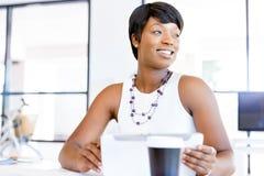 Ung kvinna i regeringsställning som använder minnestavlan Arkivfoton