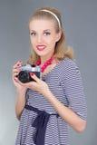 Ung kvinna i retro kläder som poserar med den gammala fotokameran Arkivfoton