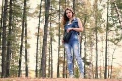 Ung kvinna i riven sönder jeans i skogen Arkivbild
