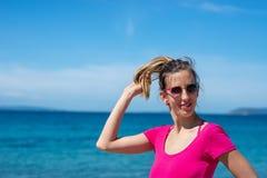 Ung kvinna i rosa skjorta som tycker om ferier på sjösidan arkivfoto
