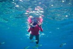 Ung kvinna i rosa swimwearsimning i det tropiska havet och ljus fisk Royaltyfri Foto