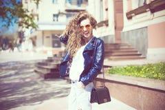 Ung kvinna i runt hipstersolglasögon och läderomslag med Arkivbild