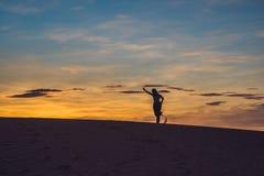 Ung kvinna i sandig öken för rad på solnedgången Royaltyfri Fotografi
