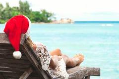 Ung kvinna i Santa Claus hattsammanträde i chaisevardagsrum på den tropiska havsstranden Arkivbilder