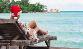 Ung kvinna i Santa Claus hattsammanträde i chaisevardagsrum på den tropiska havsstranden Arkivfoton