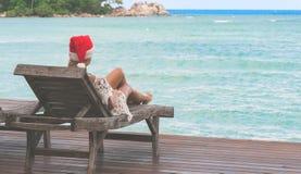 Ung kvinna i Santa Claus hattsammanträde i chaisevardagsrum på den tropiska havsstranden Royaltyfria Bilder