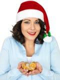 Ung kvinna i Santa Hat Holding Chocolate Money Fotografering för Bildbyråer