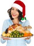 Ung kvinna i Santa Hat Holding Roast Turkey och grönsaker Royaltyfri Foto
