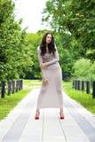 Ung kvinna i sexig lång grå färgklänning Royaltyfria Bilder