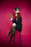 Ung kvinna i similituden av hattmakareläseboksammanträdet Royaltyfri Foto