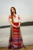 Ung kvinna i slavisk vitrysk nationell original- dräkt utomhus Arkivfoto