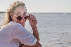 Ung kvinna i solglasögon med framkallande hår som ler Begrepp Fotografering för Bildbyråer