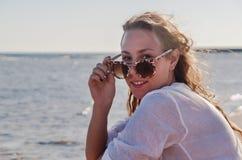 Ung kvinna i solglasögon med framkallande hår som ler Begrepp Arkivfoton
