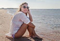 Ung kvinna i solglasögon med framkallande hår som ler Begrepp Arkivfoto