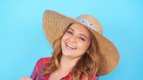 Ung kvinna, i solglasögon och att le för hatt lager videofilmer