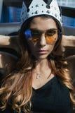 Ung kvinna i solglasögon och en krona Arkivfoto