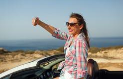 Ung kvinna i solglasögon som gör självståendesammanträde i caen fotografering för bildbyråer