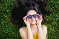 Ung kvinna i solglasögon som ligger på en grön gräsmatta och ler, bästa sikt Arkivbild