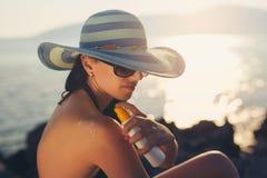 Ung kvinna i solglasögon som rymmer flaskan av sunscreenlotion royaltyfria bilder
