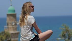 Ung kvinna i solglasögon som tycker om havssikten under semester lager videofilmer