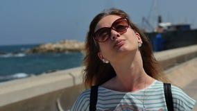 Ung kvinna i solglasögon som tycker om solen som går på kusten arkivfilmer
