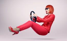 Ung kvinna i solglasögonchaufförbil med ett hjul Royaltyfri Foto