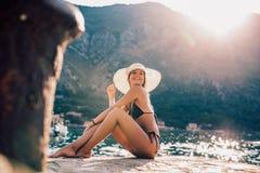 Ung kvinna i solhatt på stranden över havet royaltyfri foto