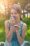 Ung kvinna i sommarklänningen som rymmer en kopp te Arkivfoto