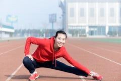 Ung kvinna i sportkläder som gör sporten Royaltyfri Foto